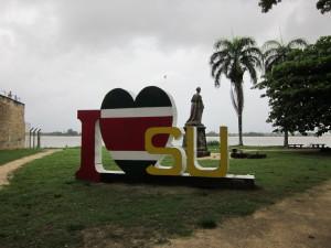 """Paramaribo, Het houten """"I love Su"""" kunstwerk. Op de achtergrond kijkt Koningin Wilhelmina uit over de Suriname Rivier (foto: René Hoeflaak)"""