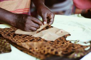 Een van de vrouwen knipt patronen voor de buckethat